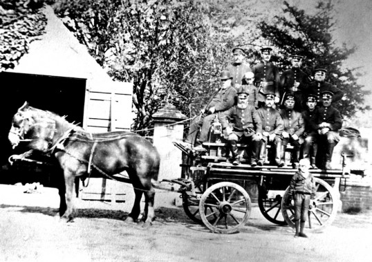 Chatteris firemen and their horse drawn vehicle. Nine firemen, one driver and a boy.. The fire station was situated to the left of St Peter's church in Market Hill. The pillar in the cen