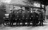 Chatteris firemen with their engine in front of Church, Chatteris. The fire station in the rear stood outside St Peter's church in Market Hill.  The pillar central in