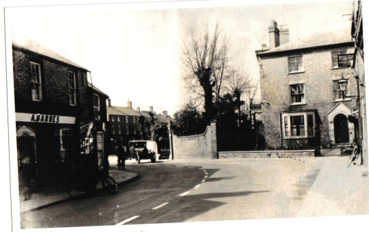 High Street, Chatteris. On the right, Bramley House and A Barnes's premises to the left. Also visible wall and gates of Chatteris House.