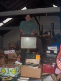 At the top of the pile, a pre digital TV, inside storage building located on New Road/ High Street , Chatteris. It is used by a Fenland Removals firm.
