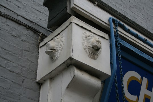 Close up of Lion Head castings on facia of shop front in High Street, Chatteris.