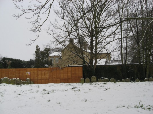 Saint Peter and Saint Paul church  grounds  with the view of a private dwelling previously 'The Old Vicarage' Chatteris on a cold and snowy day