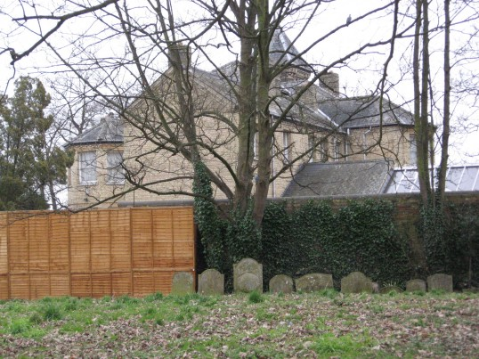 Tombstones visible at the back of the grounds  of Saint Peter & Saint Paul Church,Chatteris with the view of 'The Old Rectory' in the distance