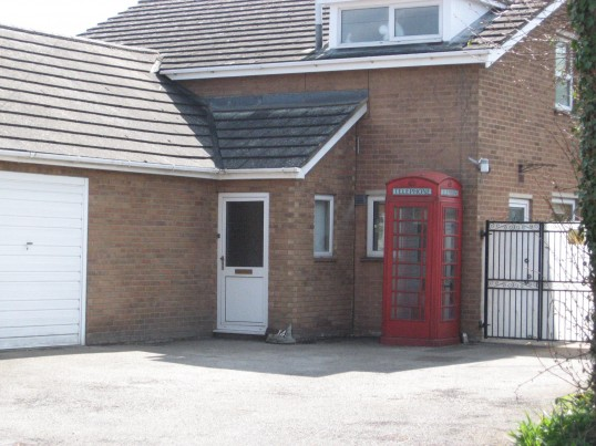 A dwelling  house in  Saint Martins Road Chatteris, with an old  original  red telephone box positioned in the front garden.