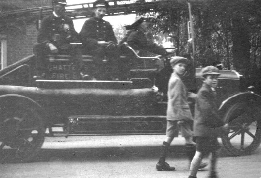 3 firemen on Chatteris Motor Fire engine (used 1928-1941) with 2 children in unnamed parade.