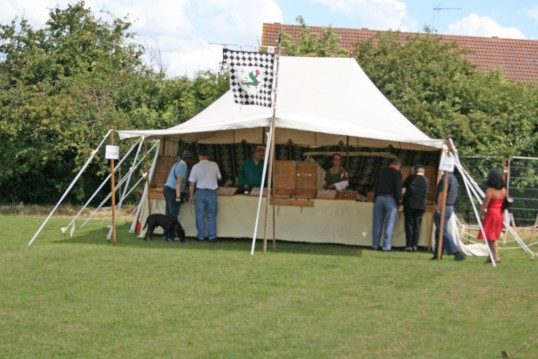 Chatteris Medieval Festival, coin minting stall on Furrowfields Park, Chatteris, creating interest in Medieval wear on sale.