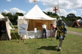 Knight on his way to Battleground walks past stall offering Crossbow practice at Chatteris medieval Festival. Chatteris