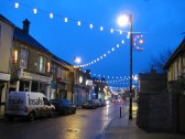 Chatteris High Street on a cold, wet, December evening, with Christmas lights cheering up the street scene.