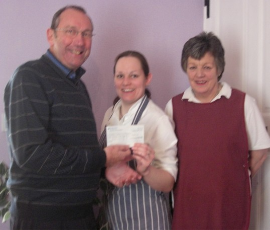Bill Haggata CCAN, gratefully receiving cheque of £180 from Tina and Gloria Prior of The Old Bakery Tea room, Chatteris as a result of their Christmas Draw.