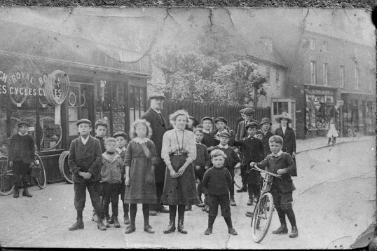 Children and bicycle on High street with Fitch's shop in background