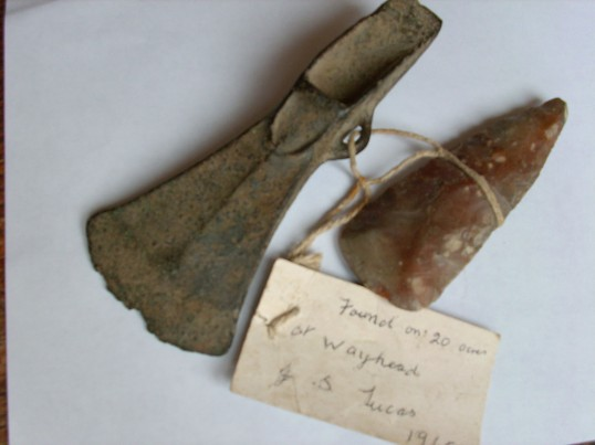 1700's.  Stone axe/spear head and cast metal cutting implement.  Both found in a field in Wayhead in 1965 by J Lucas.