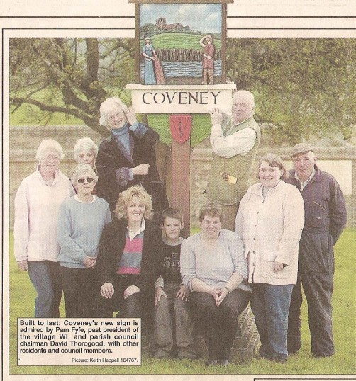 2007. Carved by a man who carved many of the Norfolk village signs, the coveney sign had deteriorated and  here a new sign is being installed.