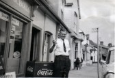 A well known Forham resident Mr Ivan Nicholls outsidehis shop in Carter Street.