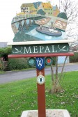 Mepal Village sign with the emblem of the New Zealand 75th Squadron attached