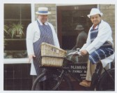 Michael Braysher (butcher) and Ian Rumbold (former delivery boy) outside the butcher's shop in High Street, Orwell, with restored delivery bicycle.