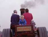 Richard Adam Flack (Richie) on a traction engine belonging to his grandfather, Essie Flack.  Richie's father, Clive Flack, on left