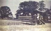 First combine harvester to be used in Orwell. Owned by H.J. Peters of Manor Farm, Orwell. St Andrew's church is visible in the distance.