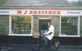 Michael Braysher, the Orwell butcher,and restored delivery bicycle, in front of High Street butcher's shop