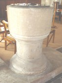 The font in St. Andrews Church, made of Freestone and lined with lead. Probably Norman. Stands on a much later stone of clunch.. Freestone
