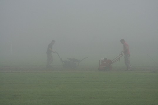 Shaun Butcher and Steve Saberton carrying out maintenance to the Pymoor Cricket pitch on a foggy autumn morning, 2006.