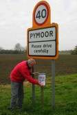 Roger Davis putting up a poster to advertise a forthcomimg event at the Pymoor Social Club.