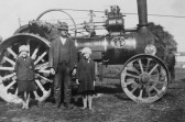 Peggy and Freda Graham with Lewis Pate by a steam engine in Pymoor.