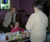 Pat Golding's grandchild, Olivia, enjoys the perks of her Gran being in charge of the cake stall at the Pymoor Methodist Chapel Christmas Bazaar 2007.