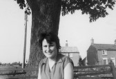 Cynthia Parson (nee Saberton) sitting on the seats under the Conker Tree at the crossroads in Pymoor.