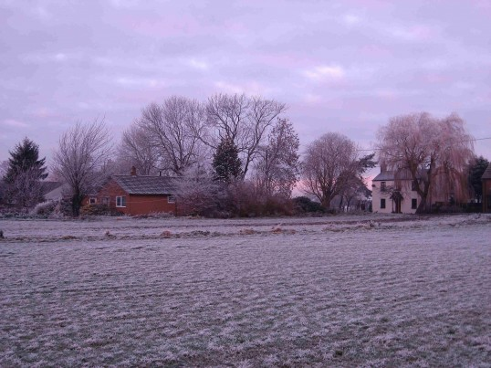 Houses in Pymoor Lane, Pymoor, early on a very cold and frosty morning seen from the fields, south of Pymoor Lane.