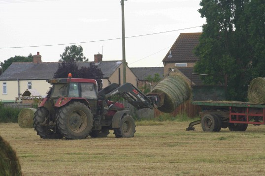 A tractor lifts a hay bale on to a trailer in a field to the south of Pymoor Lane 2007.