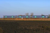 A train passes alongside Main Drove, Pymoor on its way to Ely.
