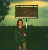 Ian Agrell, who carved the Pymoor Village Sign stands beside his work on Pymoor Hill, Pymoor, 1980.