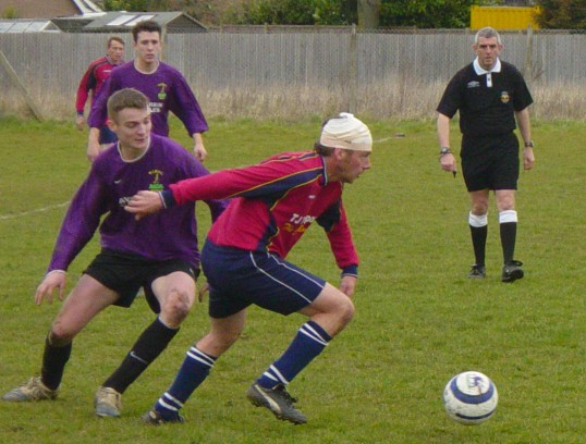 Pymoor FC Captain, Tony Ure plays on despite a head injury against Wisbech St Mary, at the Pymoor Sports Club Ground, Pymoor Lane 2006.