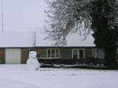 A snowman, with little prospects of longevity, stands beside a 7000 year old bog oak, in School Lane, Pymoor 2008.