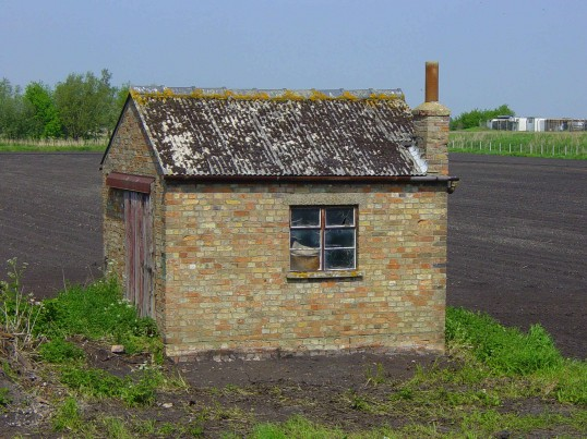 A brick built shed, near the railway crossing,  in a field alongside Black Bank Road, Pymoor, 2008.