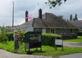 Maggie Taylor tethers a 'Flying Pig' outside Tony Rudderham's home in Pymoor Lane, Pymoor. 2008.