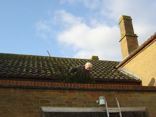 Christmas is over and Twelfth Night approaches so Alan Butcher takes down the Christmas tree on the Methodist Chapel roof in Main Street, Pymoor, 2009.