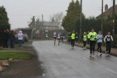 Competitors in the Annual New Year's Eve 10K Fun Run 2009  make their way down Main Street, Pymoor from the crossroads (Pymoor Hill).