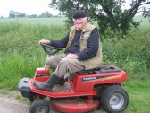 Les Barker, cutting the grass outside his bungalow in Pymoor Lane, Pymoor.