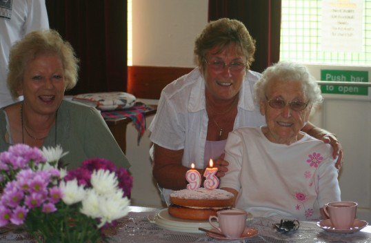 Alocha Barker, Cynthia Parson help Joan Saberton celebrate her 93rd birthday at the Coffee Afternoon in the Pymoor Cricket Club 2009.