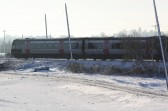 A train, heading towards Ely, passes alonside Main Drove, Pymoor, in the snow, 2009.