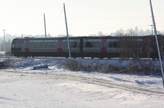A train, heading towards Ely, passes alonside Main Drove, Pymoor, in the snow.