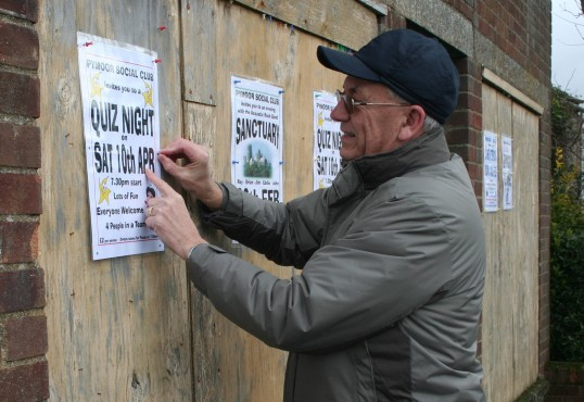 Roger Davis puts up a poster on the old Saberton Stores  advertising the forthcoming Quiz at the Pymoor Cricket & Social Club 2010.