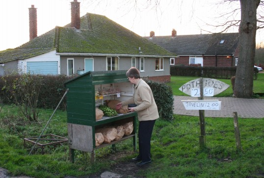 Rosemary Davis buying vegetables from Tony & Sue Rudderham's stall in Pymoor Lane, Pymoor 2008.