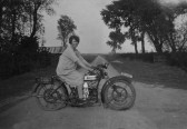 Daisy Martin on a motorbike in Pymoor Lane, Pymoor. This photo is taken looking west along Pymoor Lane, circa 1924.