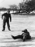 Roger Parson of Pymoor takes a tumble on the ice much to the amusement of fellow Pymoor farmer, Basil Taylor 1985.
