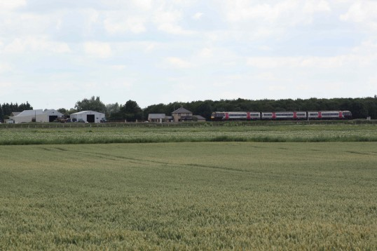 A diesel passenger train passing Laurel Farm, Main Drove, Little Downham, Pymoor, 2011.
