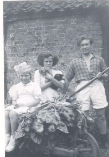 Mary & Sylvia Hannah with John King outside the pig sty at Oxlode Hall, Pymoor.