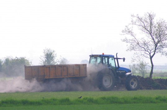 A speeding tractor & trailer in a field off Pymoor Lane, Pymoor, 2011.