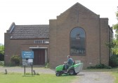 Graham Lark mowing the grass outside the Pymoor Methodist Chapel, in Main Street, Pymoor, 2011